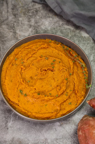 overlay mashed sweet potatoes in a grey bowl on a grey background
