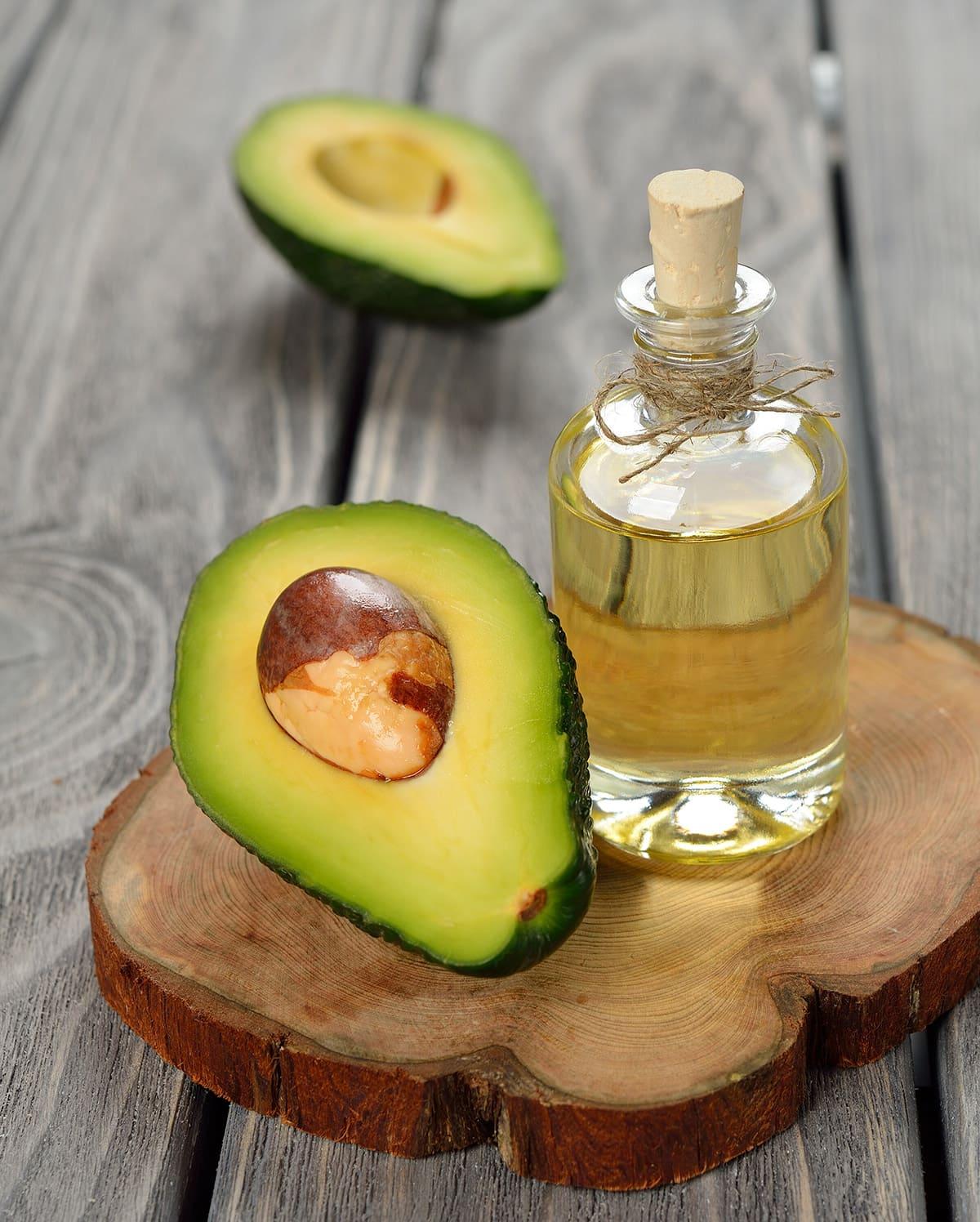 avocado oil with avocado on wooden backgound