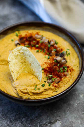 black-eyed pea hummus in a brown bowl on a grey background