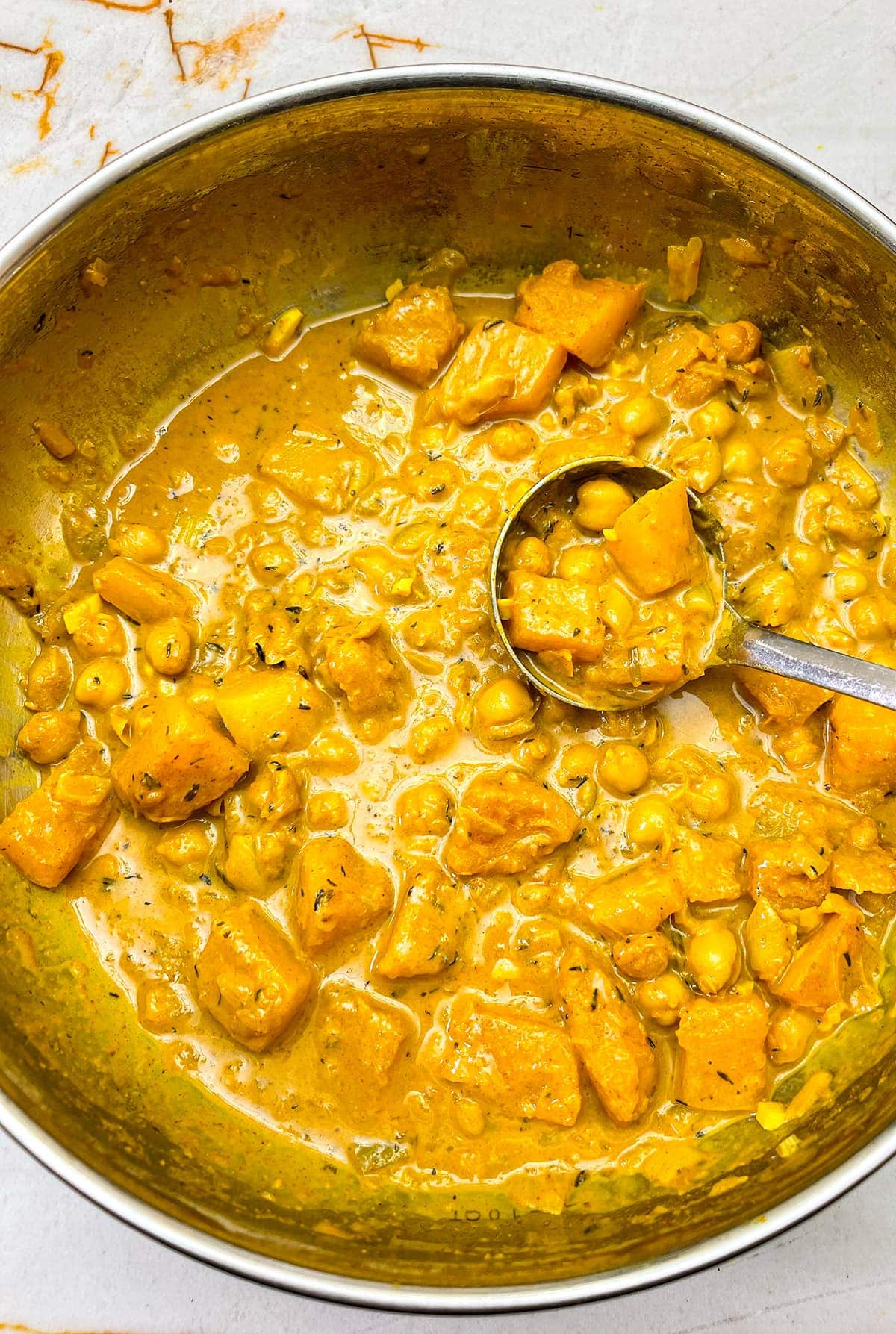 butternut squash chickpea curry in a saucepan on a beige marbled background