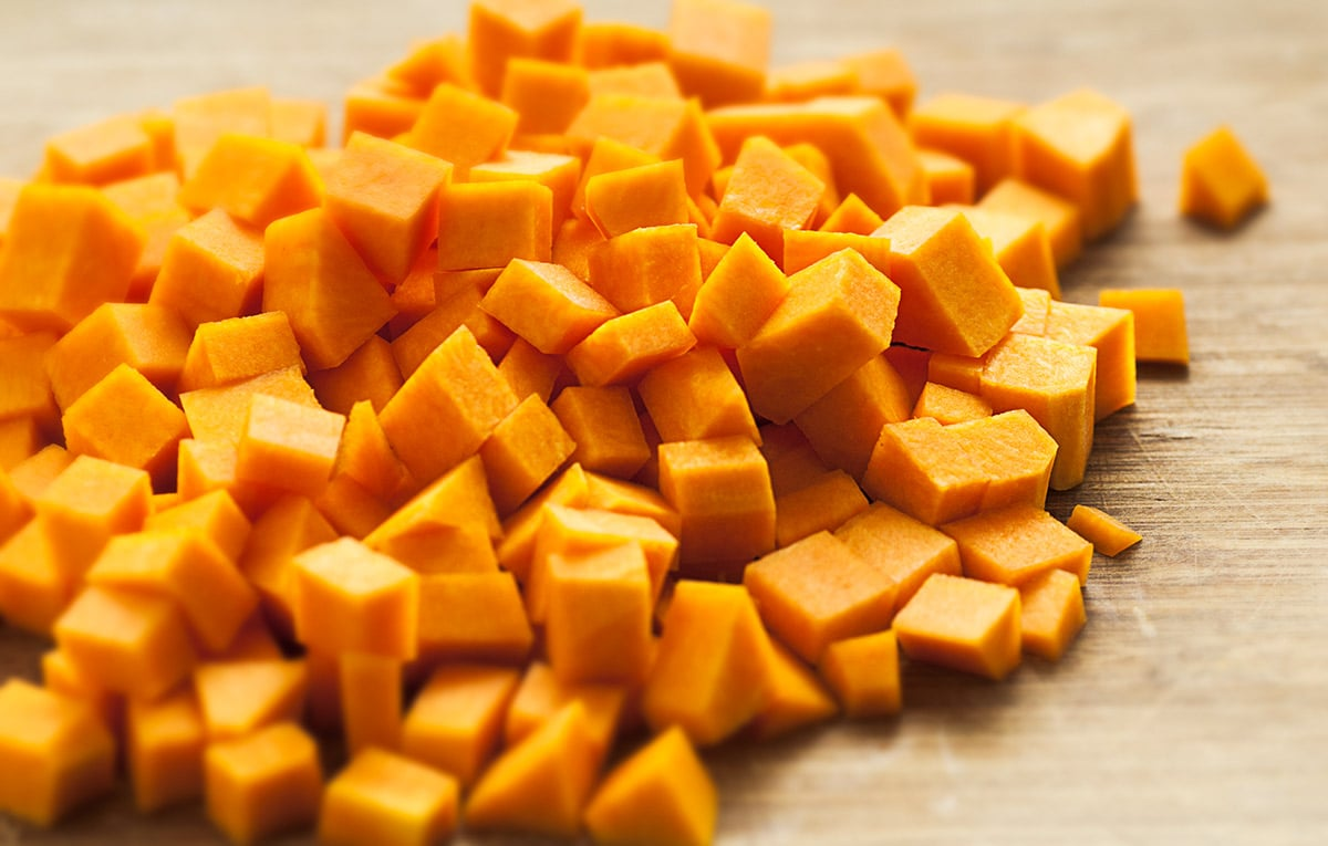 butternut squash cubes on a wooden background