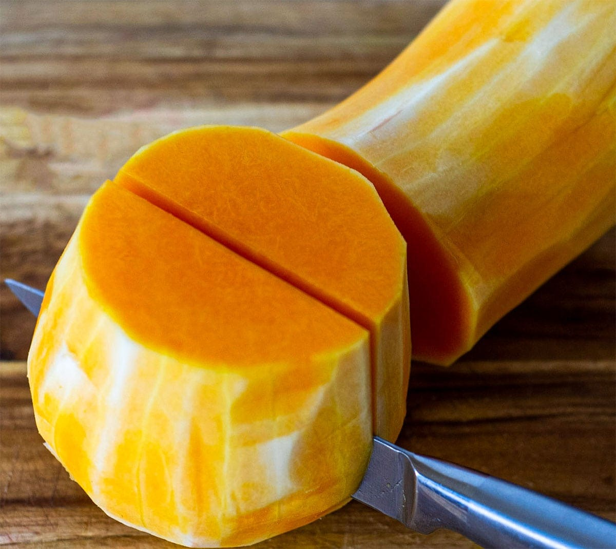 how to peel butternut squash, cutting butternut squash with a knife on wooden cutting board
