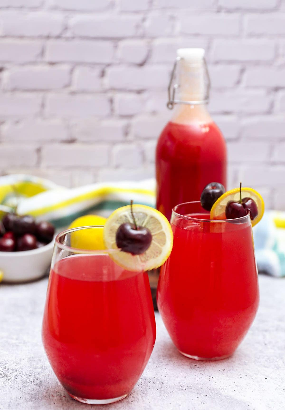 Cherry lemonade in glasses on a grey background