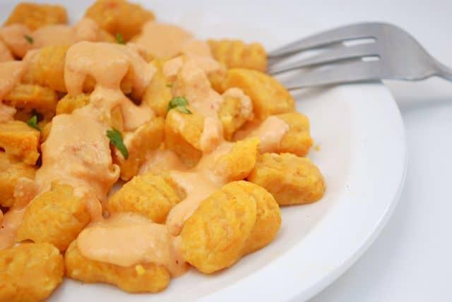 cheesy butternut squash gnocchi on white plate on white background