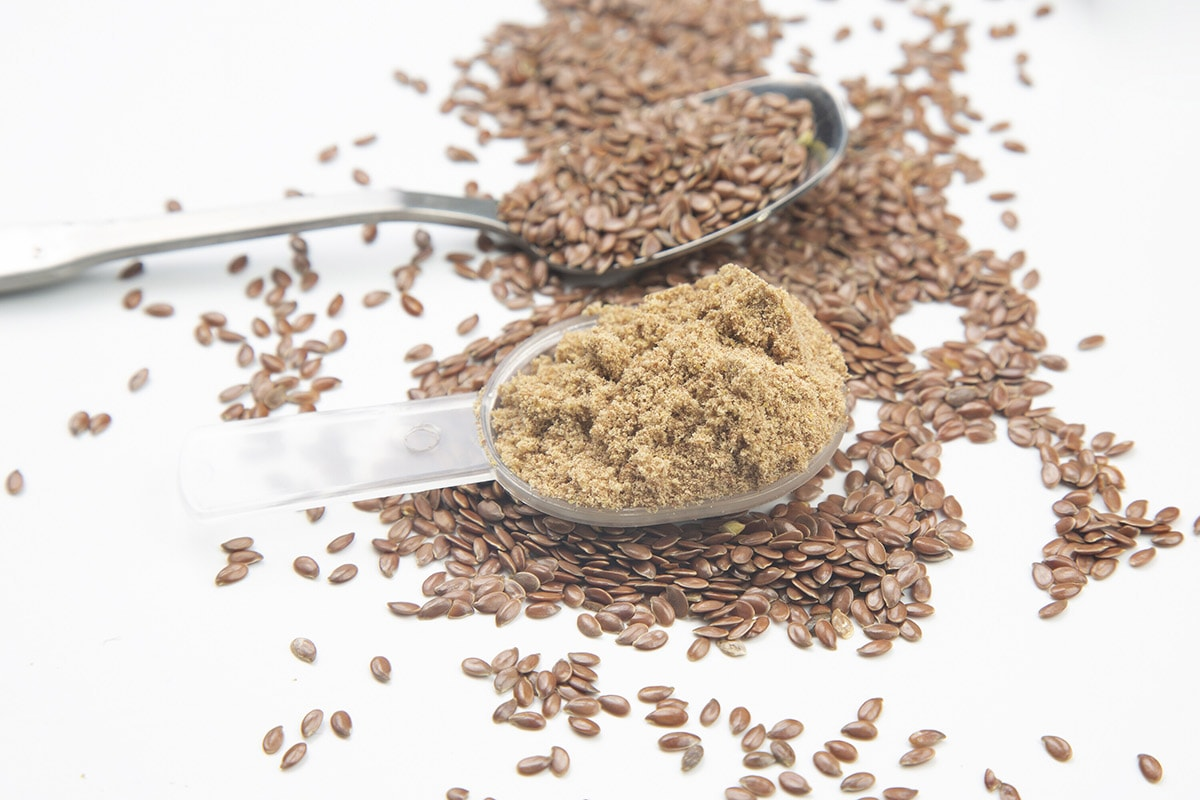 ground flaxseeds in spoon isolated on a white background