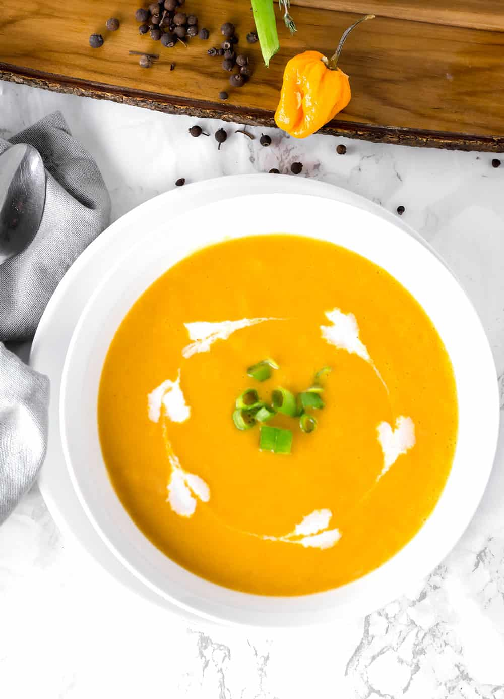 overlay Jamaican pumpkin soup in a white bowl on a white background