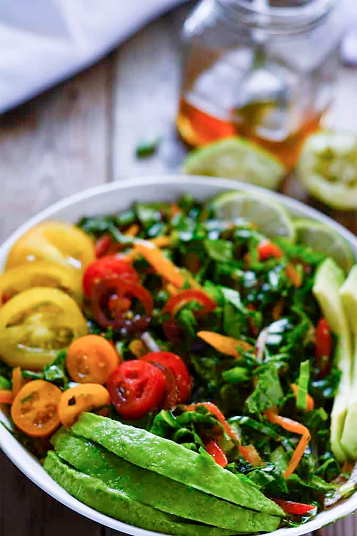 kale salad in a white bowl on a wooden background