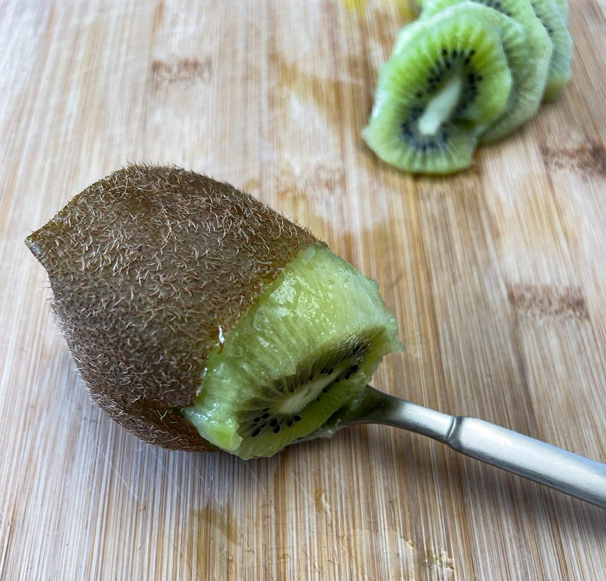 kiwi on wooden cutting board, spooning to cut