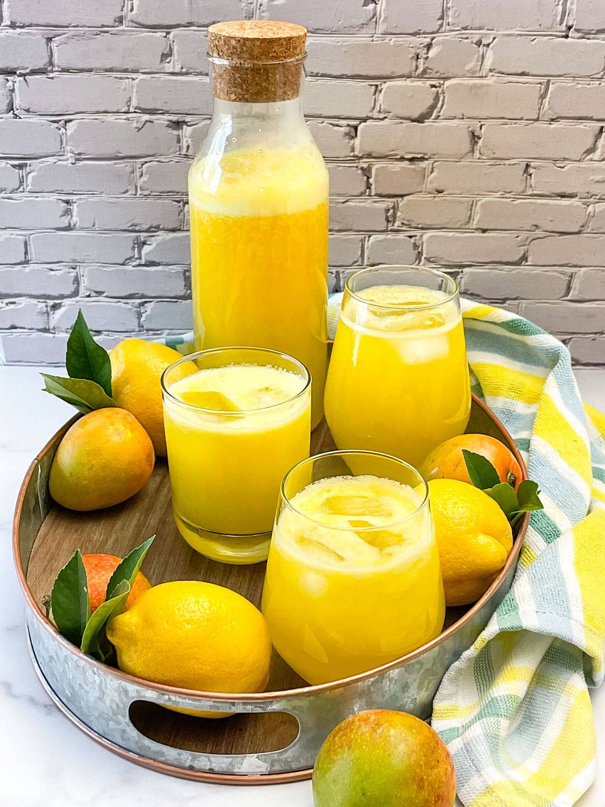 mango lemonade in a container with glasses poured