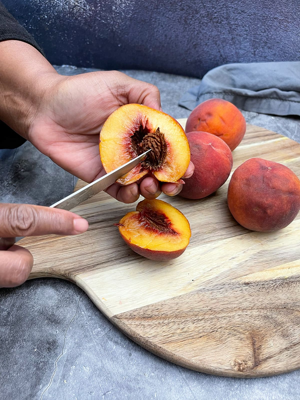 remove peach pit with paring knife on a wooden cutting board