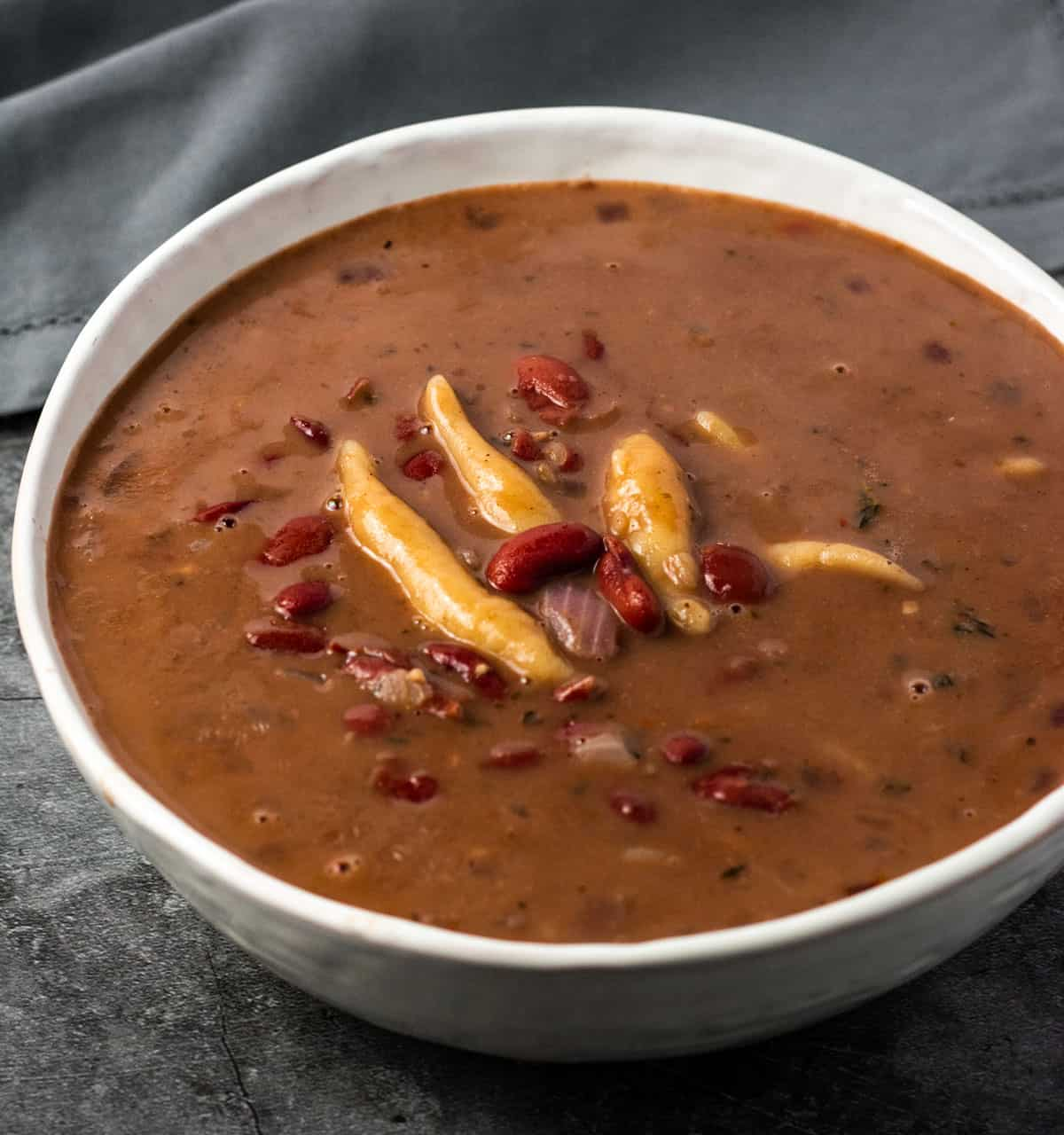 Jamaican red pea soup in a white bowl on a grey background