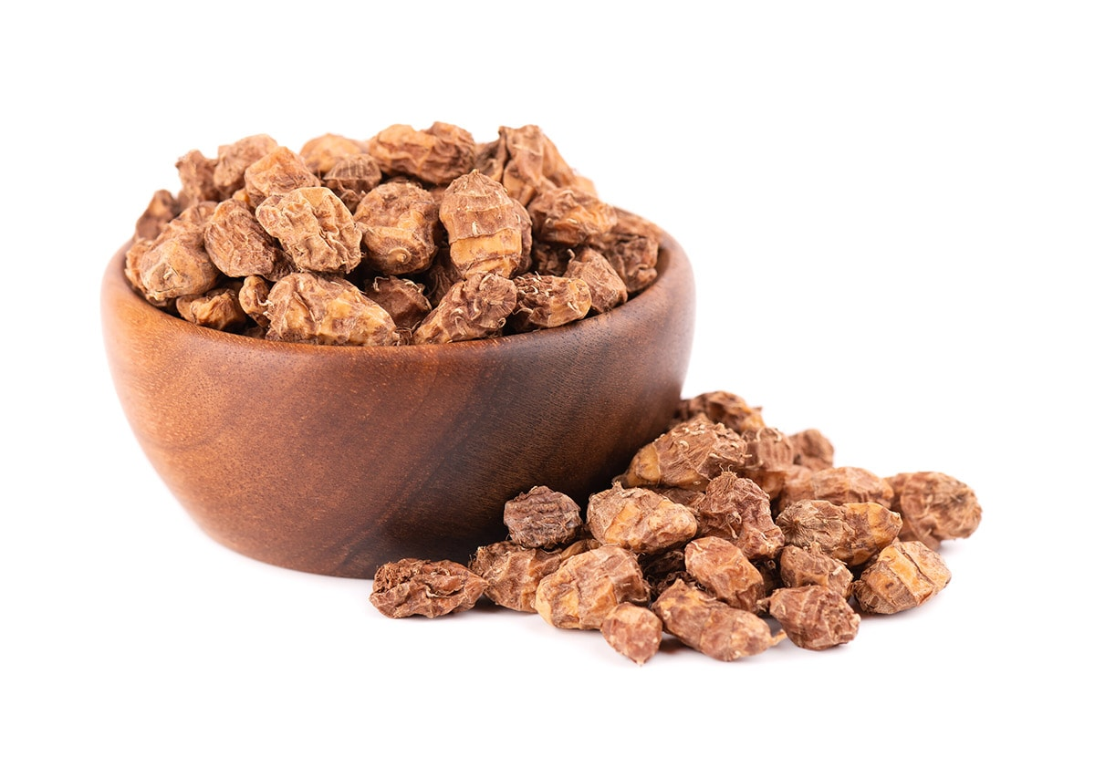 tiger nuts in a wooden bowl on a white background