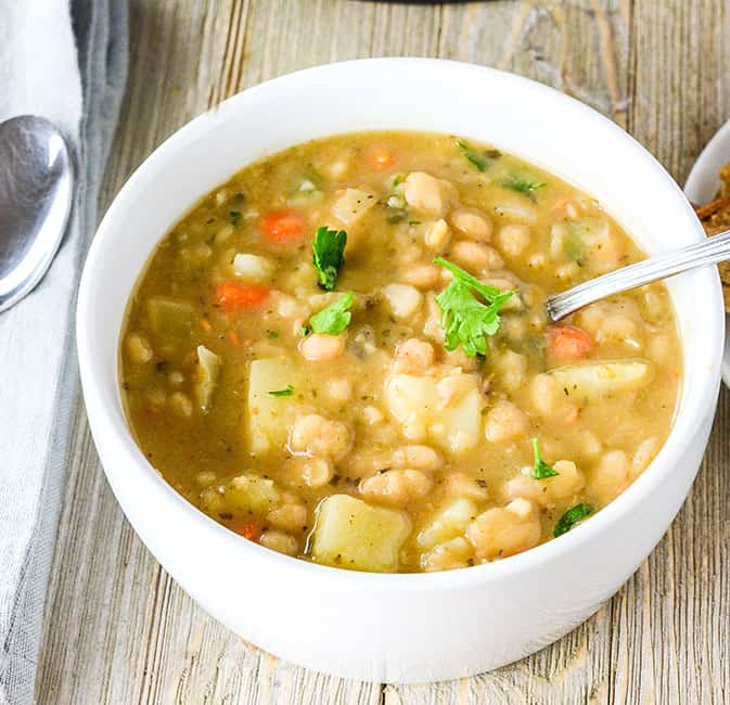 vegan white bean soup in a white bowl
