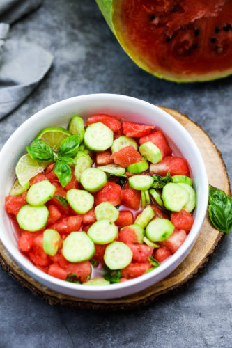 Cucumber Basil and Watermelon Salad in white bowl on wooden board on a grey background