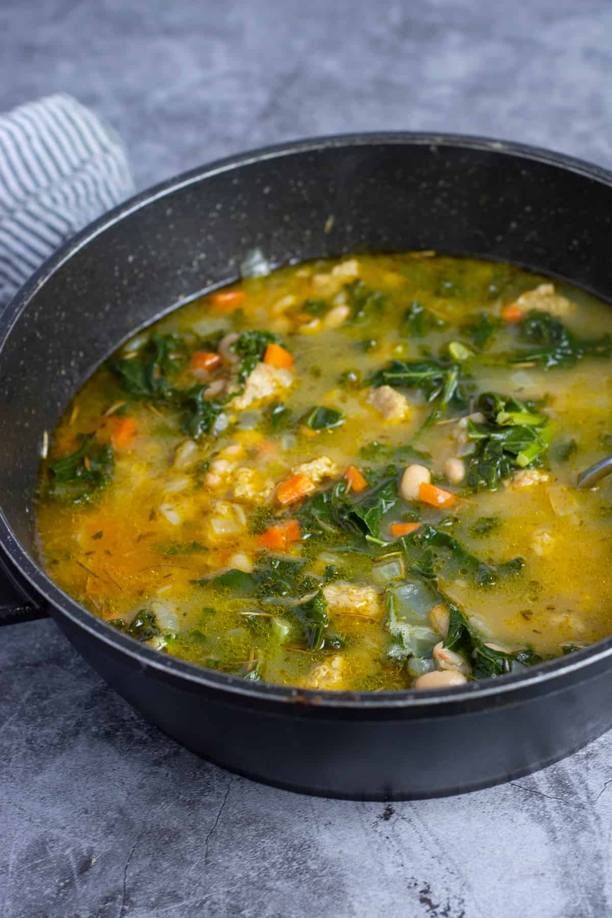 white bean and kale soup in a black bowl on a grey background