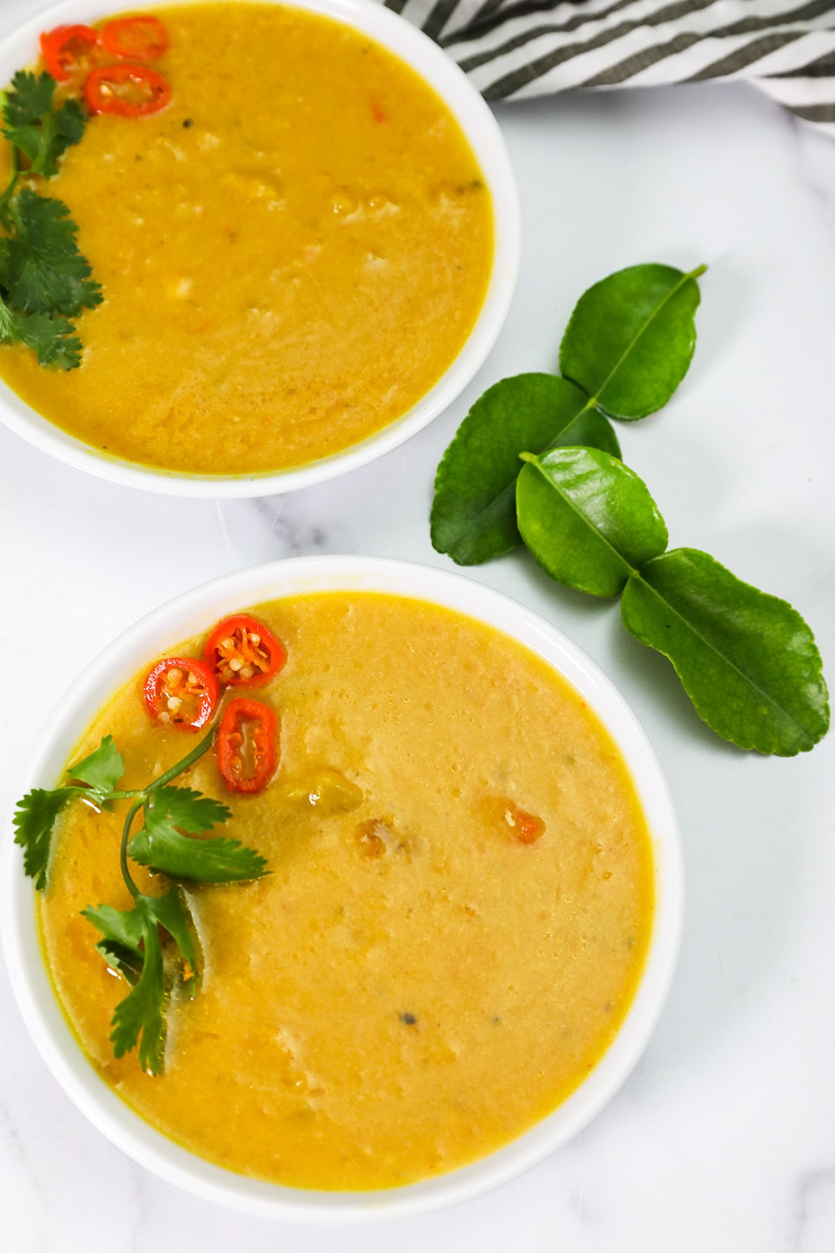 overlay of thai pumpkin soup in two white bowls on white background
