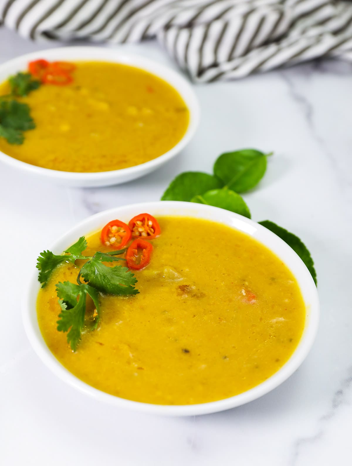 Close up thai pumpkin soup in two white bowls on white background